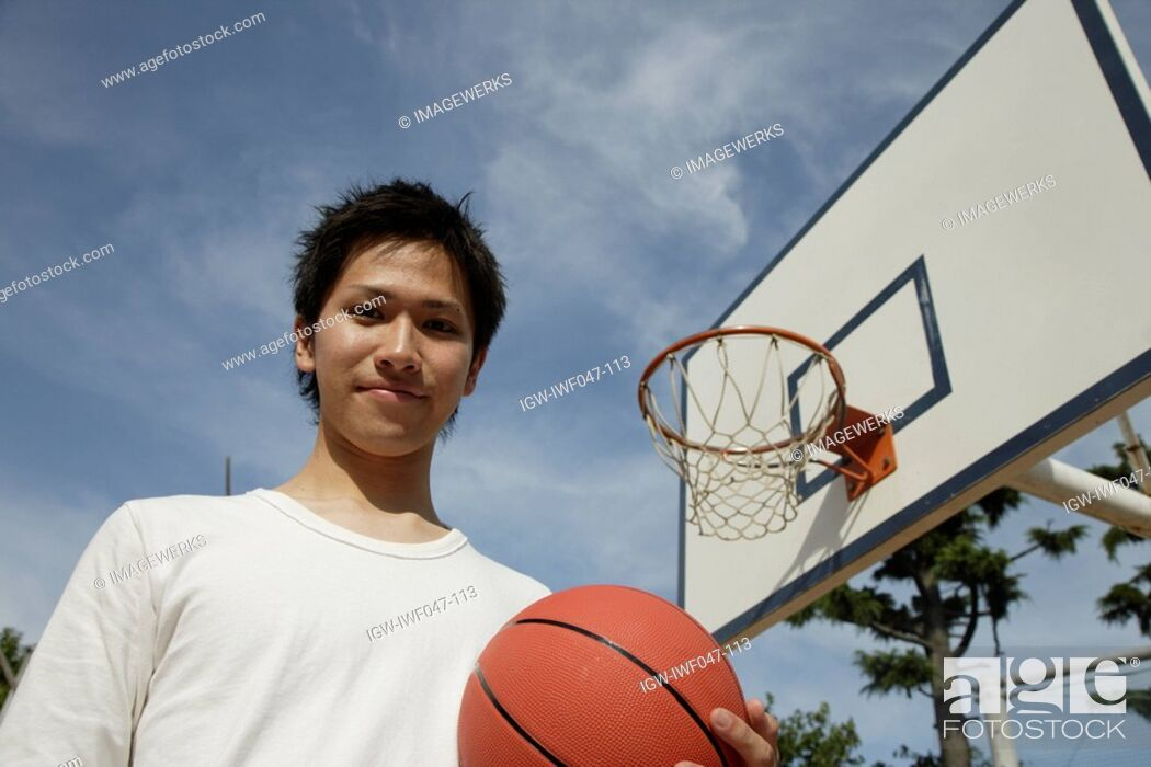 Stock Photo: Portrait of a young man holding basketball.
