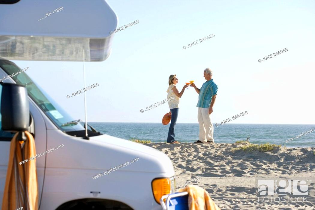 Stock Photo: Mature couple toasting with cocktails by motor home on beach, side view.
