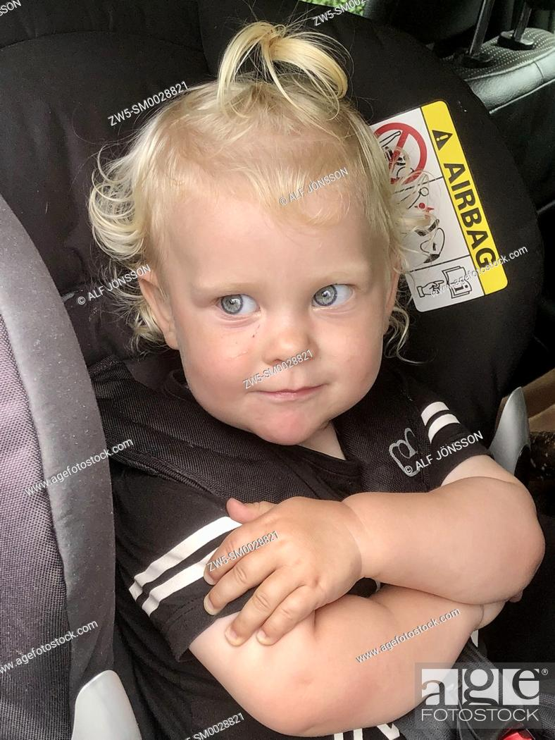 Stock Photo: Little blond girl, twu years old, in a safety car seat in Scania, Sweden.