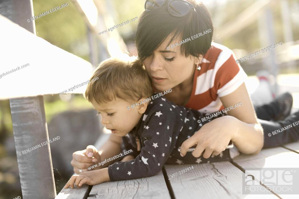 Stock Photo: caring mother laying with son on floor outdoors, exploring.