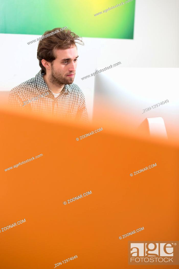 Imagen: Portrait of young creative with headphone sitting in front of computer at office.