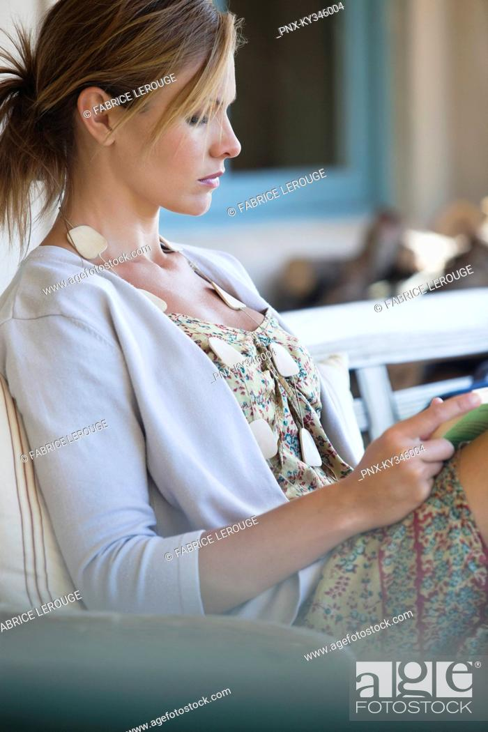 Stock Photo: Side profile of a beautiful young woman reading a book.