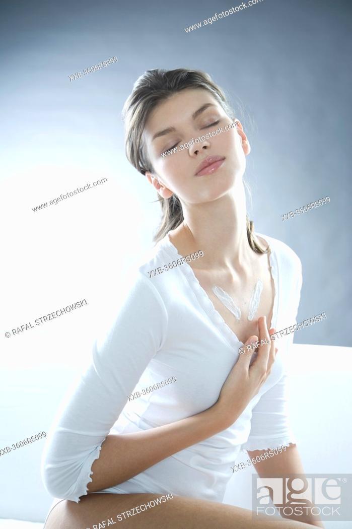 Stock Photo: young woman creaming neckline.
