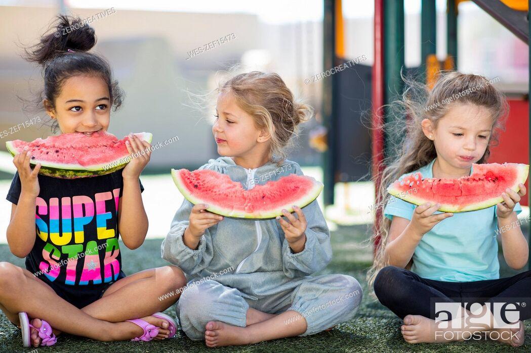 Stock Photo: Three girls eating watermelons in kindergarten.