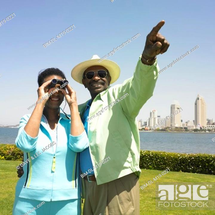 Stock Photo: African couple using binoculars with cityscape in background.