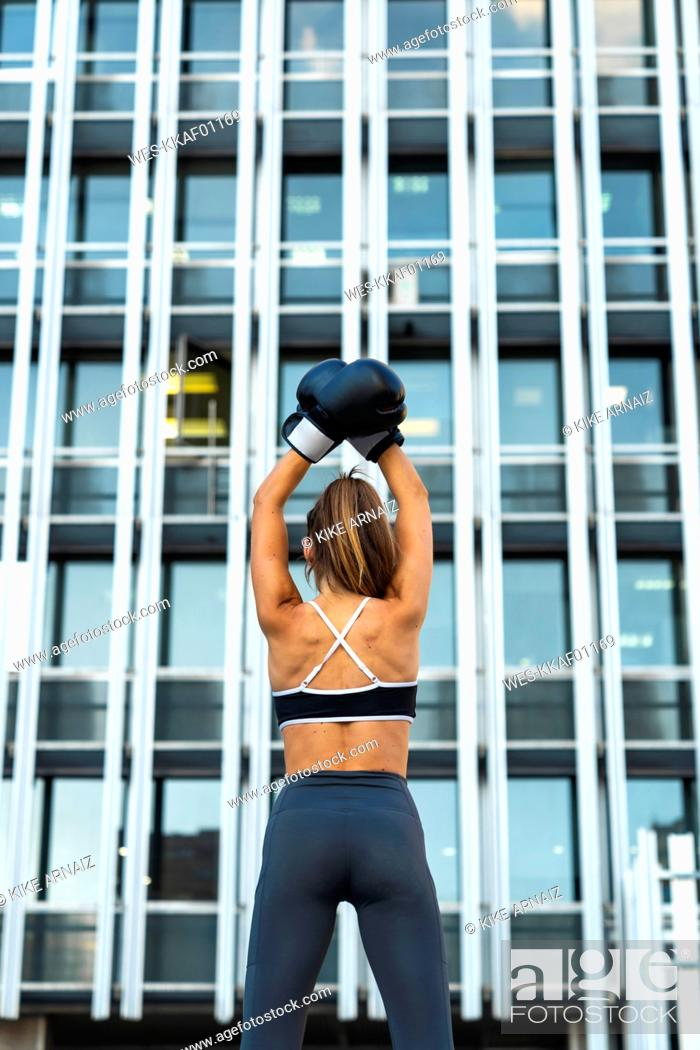 Stock Photo: Sportive young woman with boxing gloves in the city raising her arms.