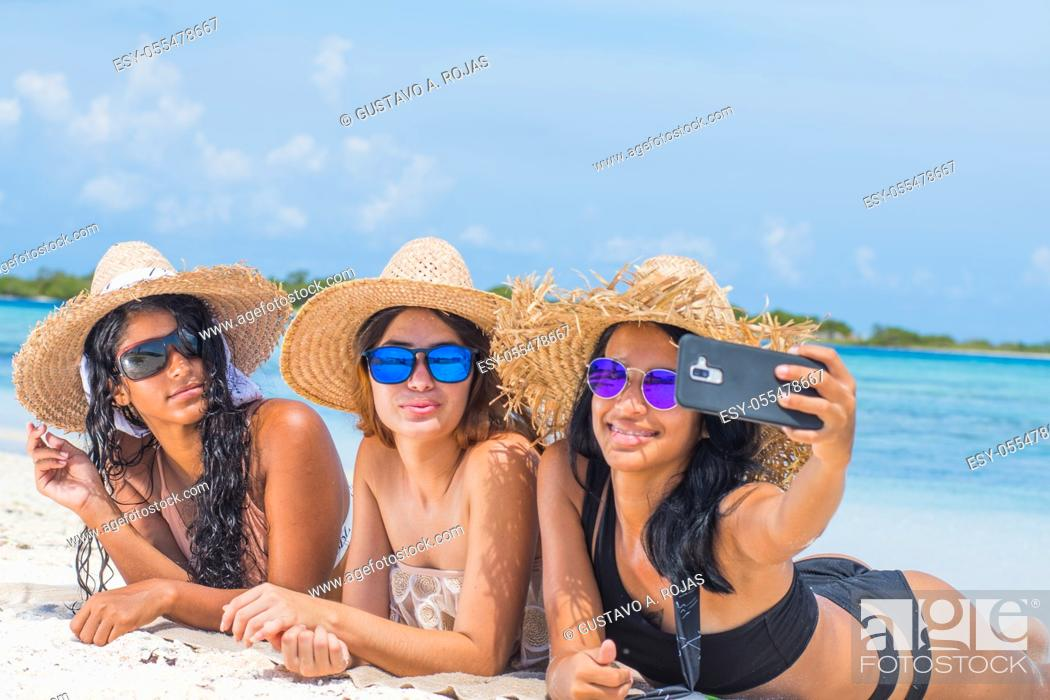 Stock Photo: three multi ethnic women friends lying back smiling and taking selfie photo with sunlight at blue water beach.