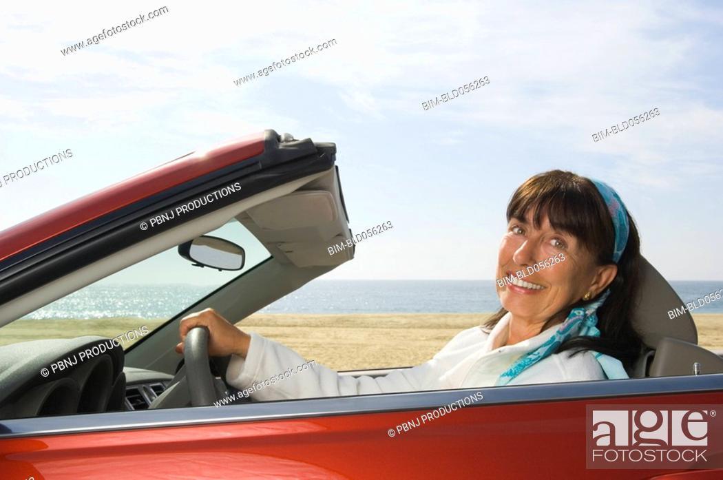 Stock Photo: Senior Hispanic woman driving convertible car.