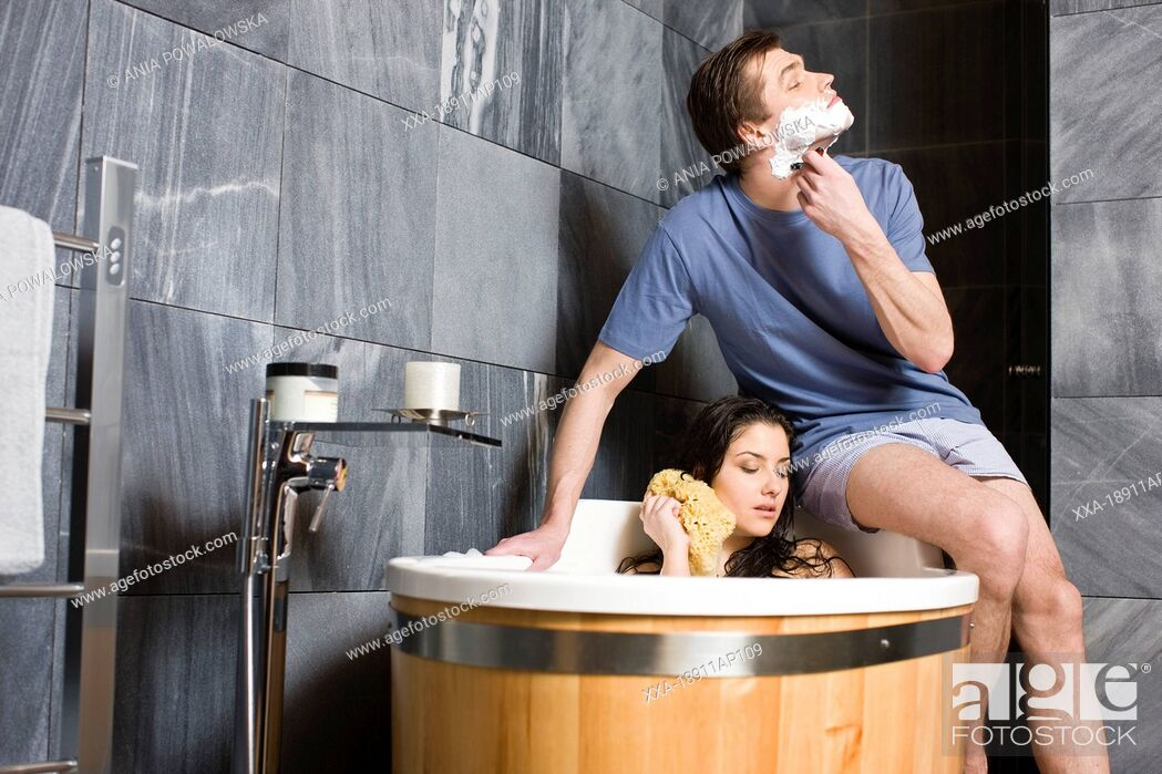 Stock Photo: Couple in bathroom. Man shaving and woman having bath.