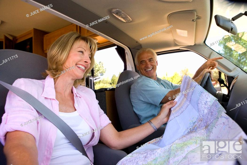 Stock Photo: Mature woman with map in motor home by husband, smiling, low angle view.