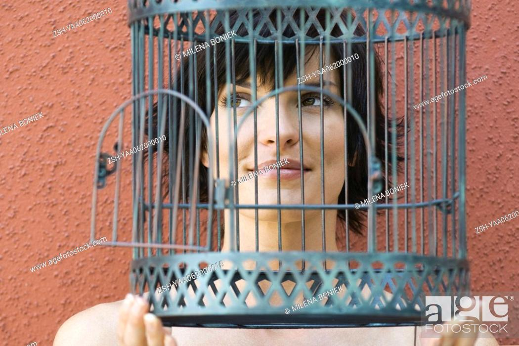 Stock Photo: Woman holding empty birdcage in front of face, smiling, looking away.