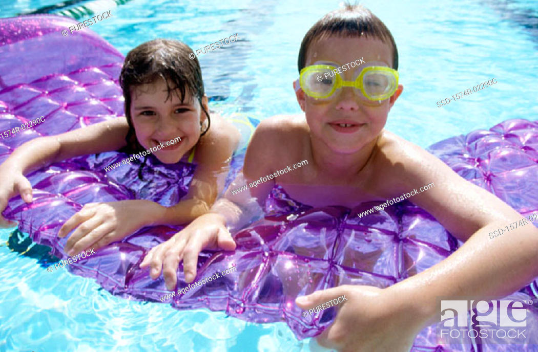 Stock Photo: Portrait of a boy and a girl leaning on a pool raft.