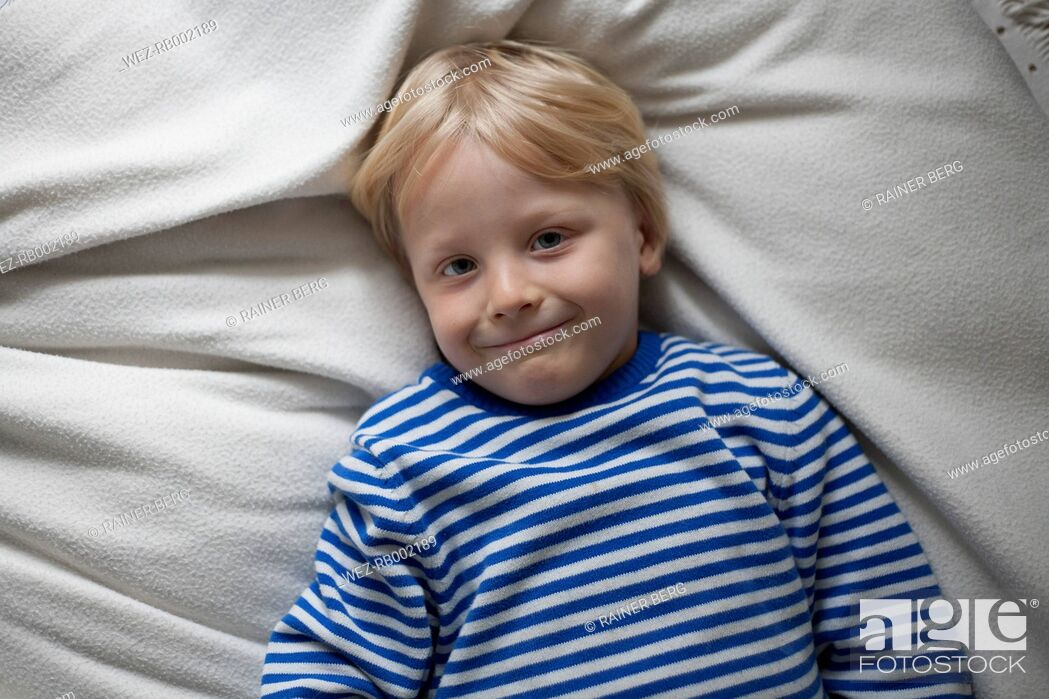 Stock Photo: Portrait of smiling little boy lying on blanket at home.