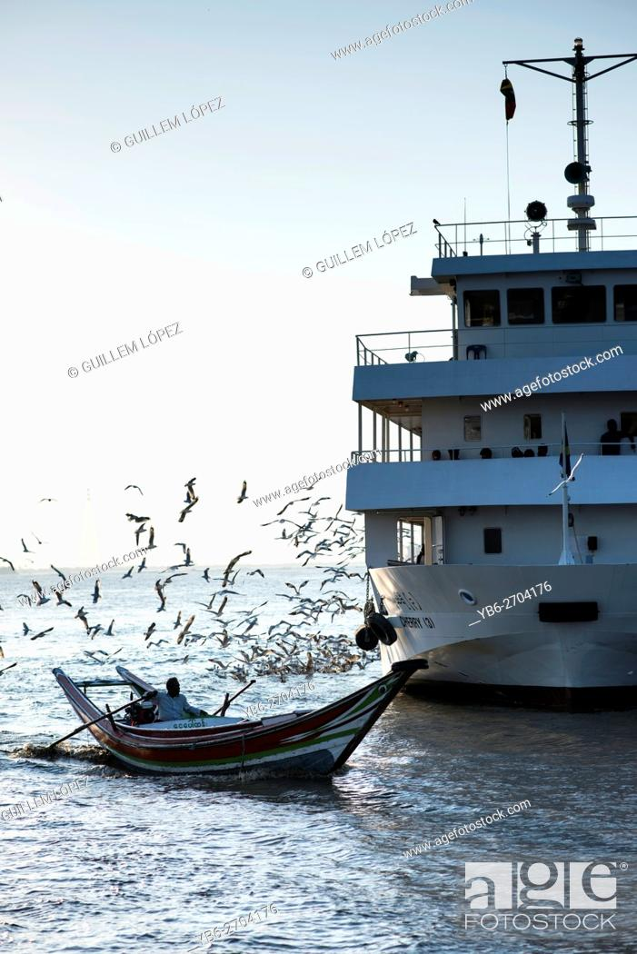 Stock Photo: A traditional long boat passing by a passenger ferry at the Irrawaddy River in Yangon, Myanmar.