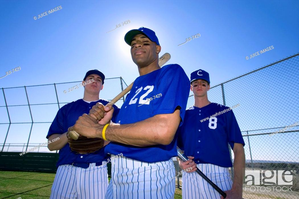 Stock Photo: Three baseball players, in blue uniforms and caps, standing on pitch, portrait, low angle view backlit.