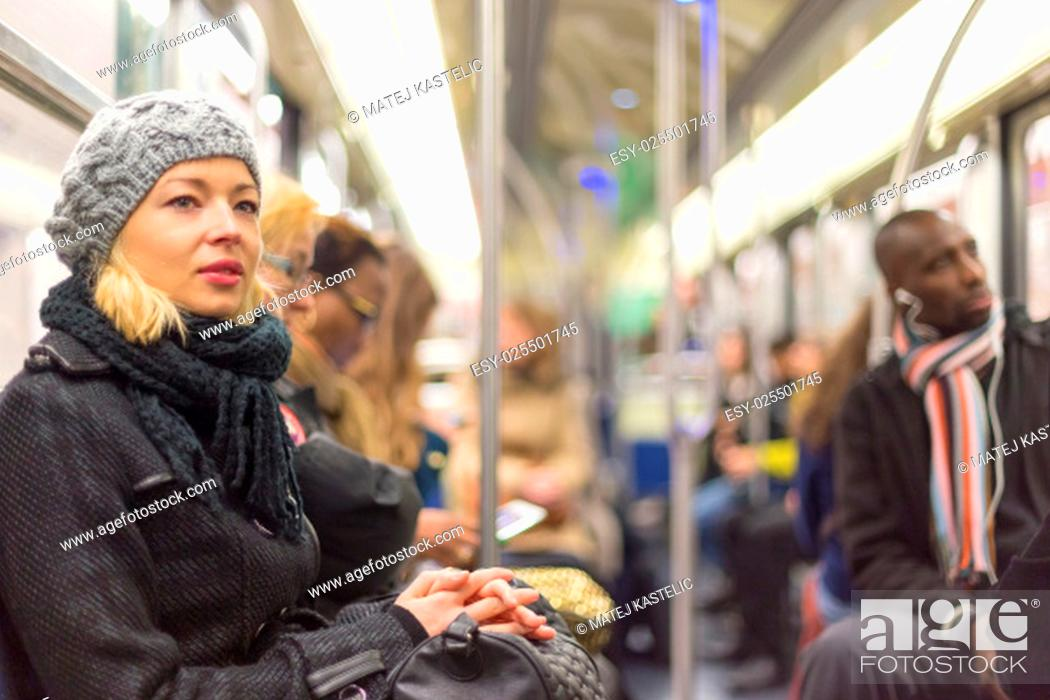 Stock Photo: Beautiful blonde caucasian lady, wearing winter coat, traveling by metro in rush hour. Public transport.