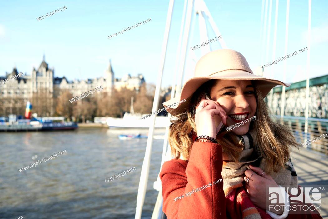Stock Photo: UK, London, stylish young woman talking on cell phone on Millennium Bridge.
