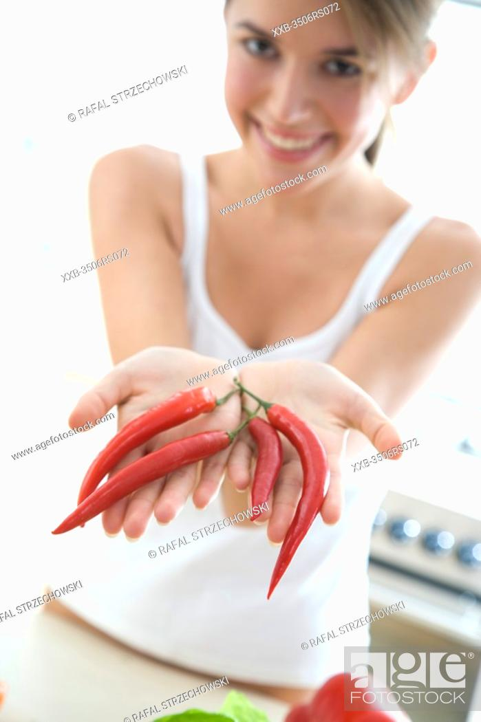 Stock Photo: young woman with chilli peppers.