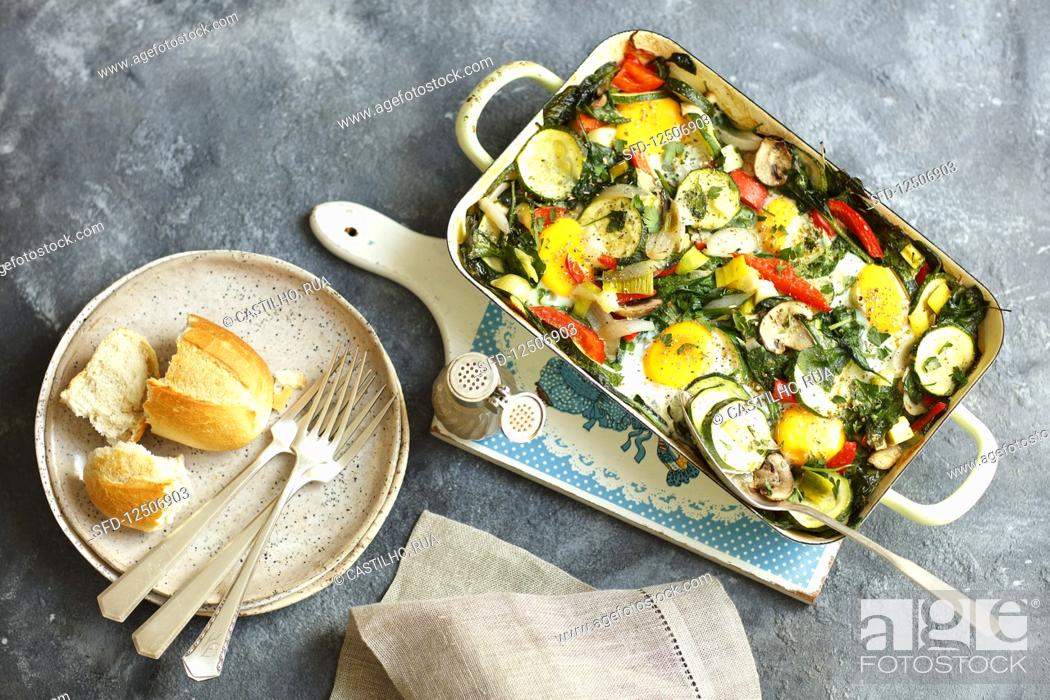 Stock Photo: Eggs with oven-baked vegetables in a baking dish.