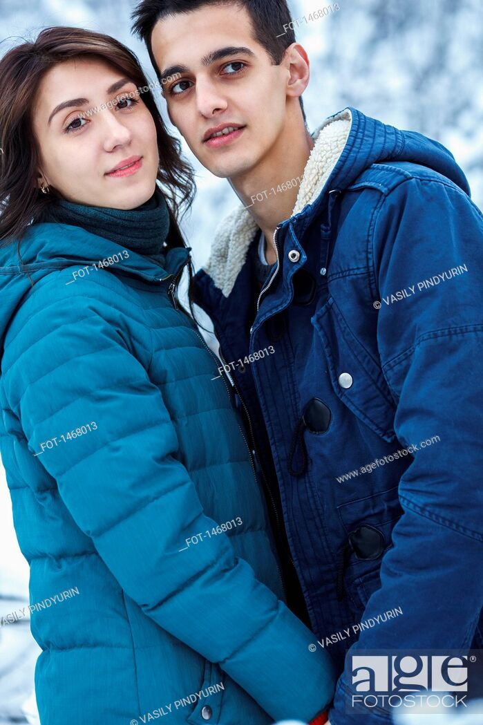 Stock Photo: Loving young couple in warm clothing looking away.