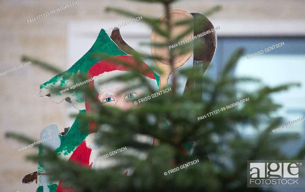 Stock Photo: A wooden Santa Clause with cooking spoons peeks through a christmas tree in Muenster, Germany, 21 November 2017. In many cities the Christmas market set up.