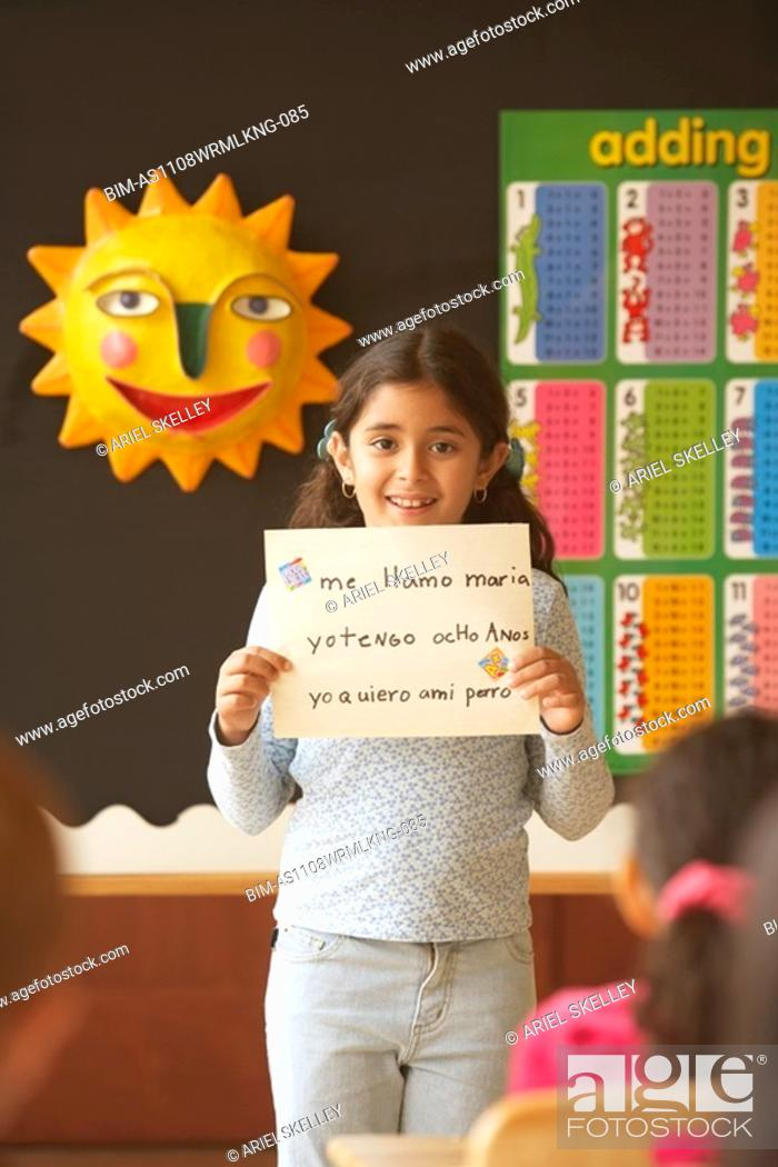Stock Photo: Young Hispanic girl holding up paper in class.