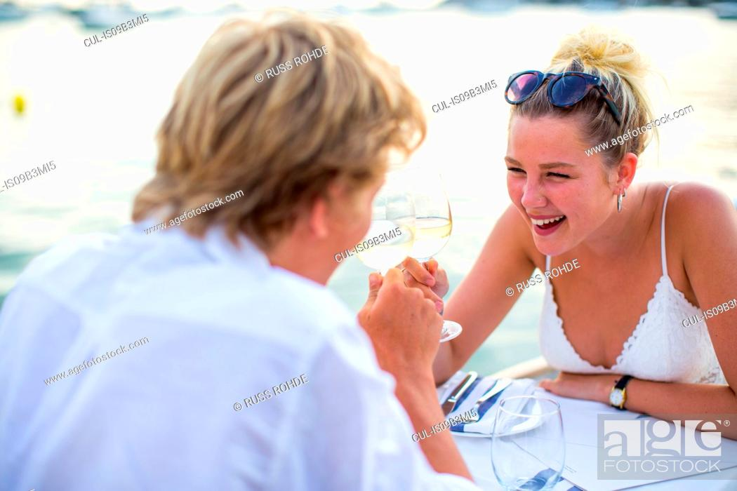 Stock Photo: Young couple laughing at waterfront restaurant, Majorca, Spain.