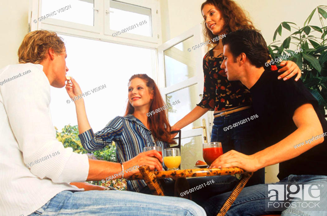 Stock Photo: A group of young people eating and drinking.
