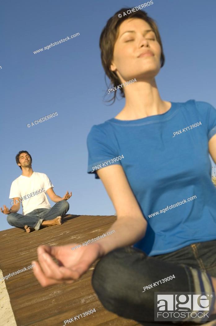 Stock Photo: Young couple in yoga attitude, outdoors.