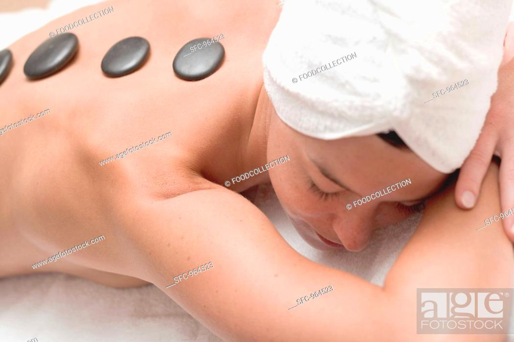 Stock Photo: Woman having LaStone Therapy healing therapy using stones.