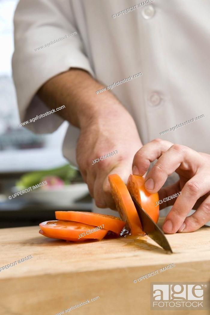 Stock Photo: Male chef slicing tomato.