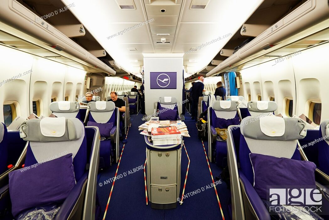 Stock Photo: Iinterior view of the lower deck of an Airbus A380 jet airliner owned by the german airlines Lufthansa. Passengers are just boarding and finding their seats.