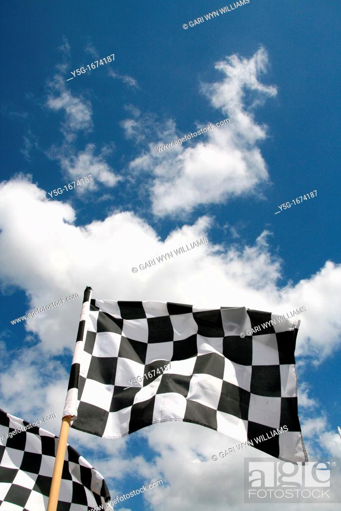 Stock Photo: grand prix chequered flags flying in wind and blue sky.