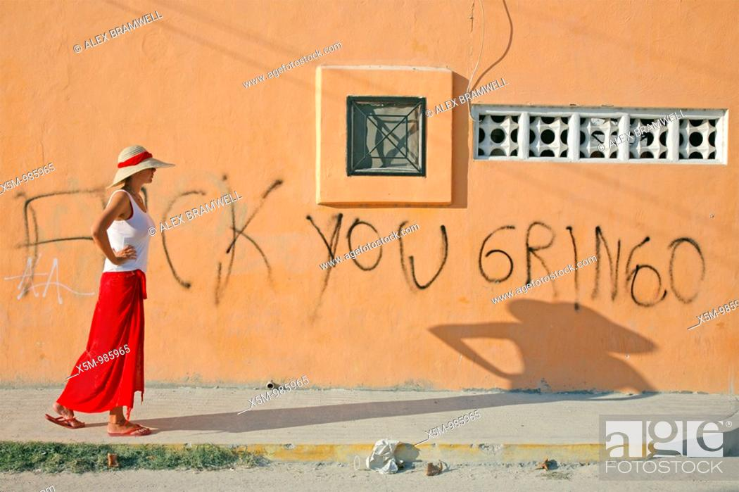 Stock Photo: Tourist walking past a bit of anti-American grafitti on a wall in Playa del Carmen, Mexico.