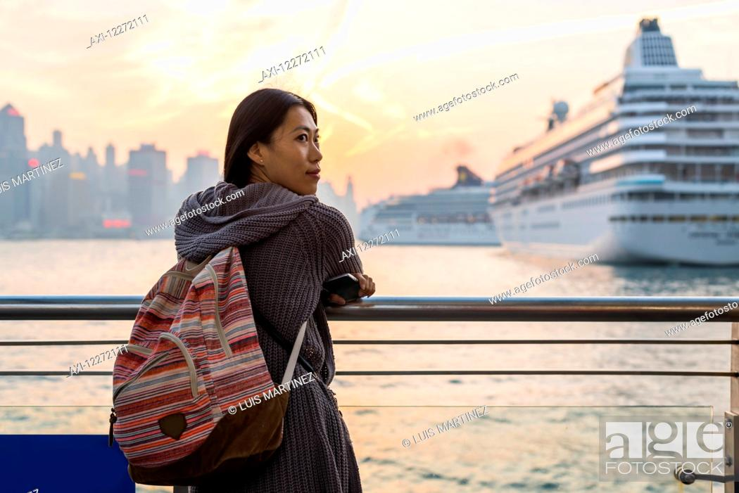 Imagen: A young woman at the waterfront with cruise ships in the harbour in the background, Kowloon; Hong Kong, China.