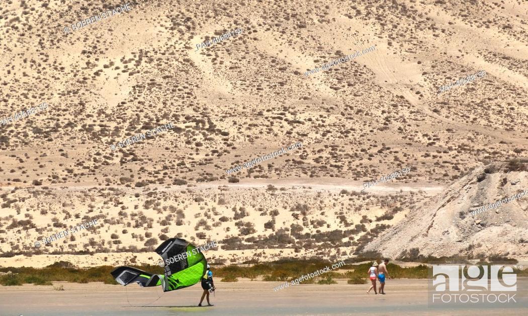 Stock Photo: A kitesurfer walks along the sandy beach of Sotavento with a green chute near Costa Calma on Fuerteventura, Spain, 05 June 2013.