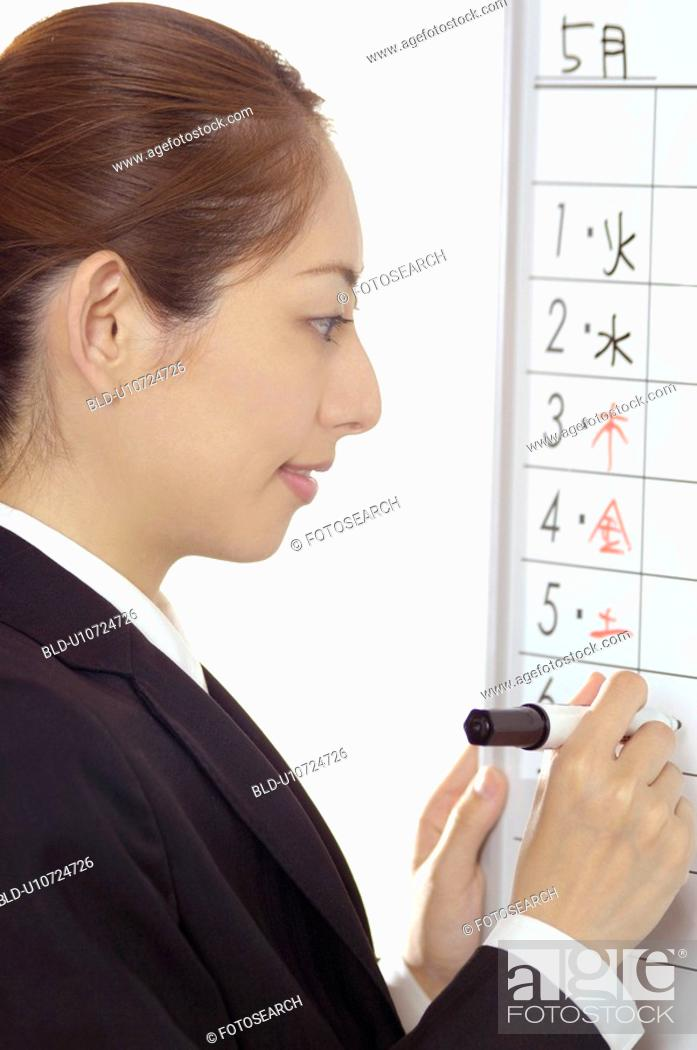 Stock Photo: Business lady who writes a schedule.