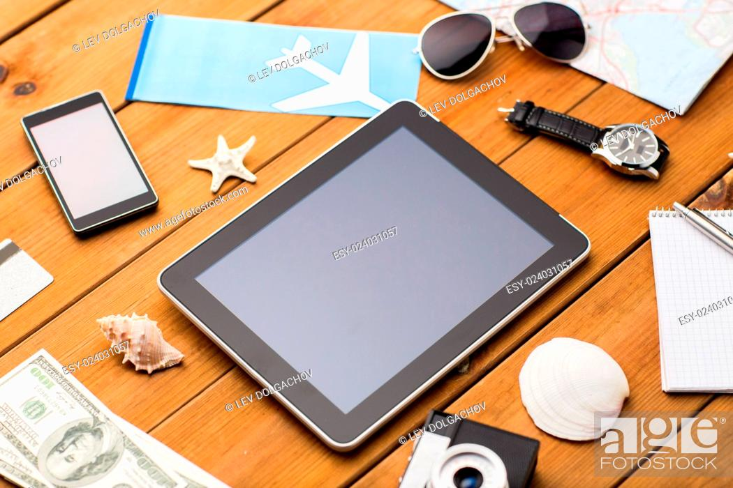 Stock Photo: travel, tourism, technology and objects concept - close up of smartphone with tablet pc computer, airplane ticket and personal stuff.