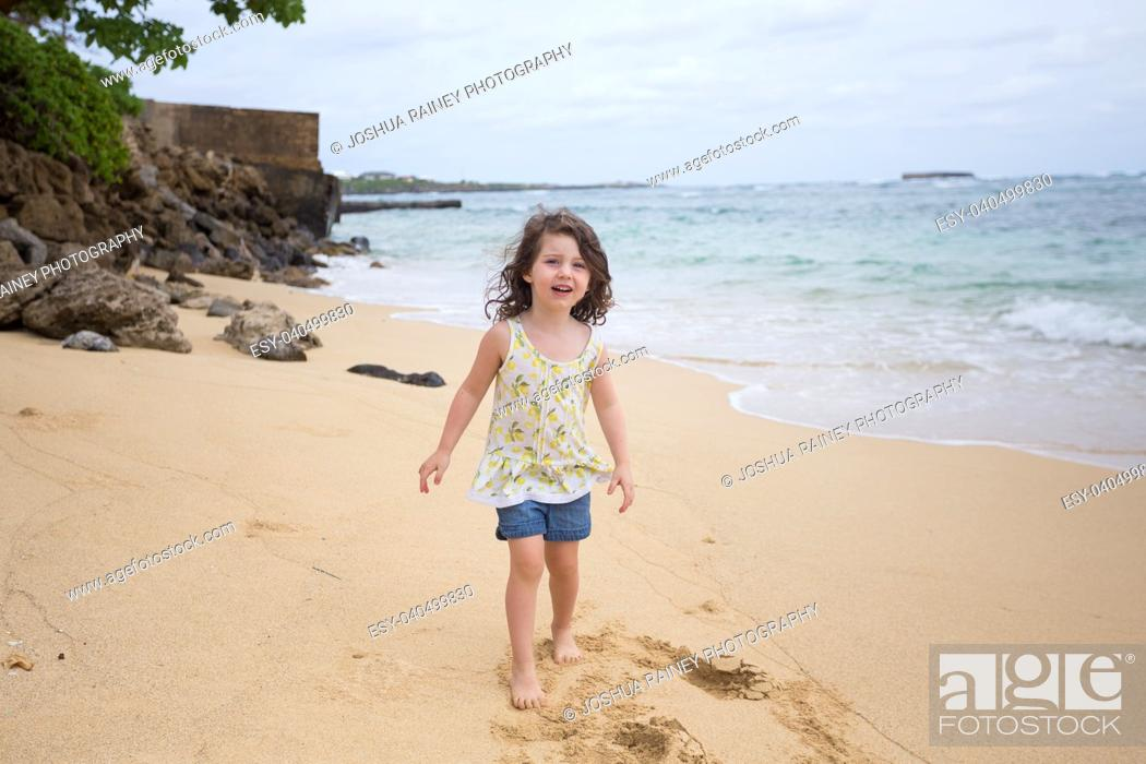 Stock Photo: Lifestyle portrait of a young three year old girl playing on the beach in Oahu Hawaii.
