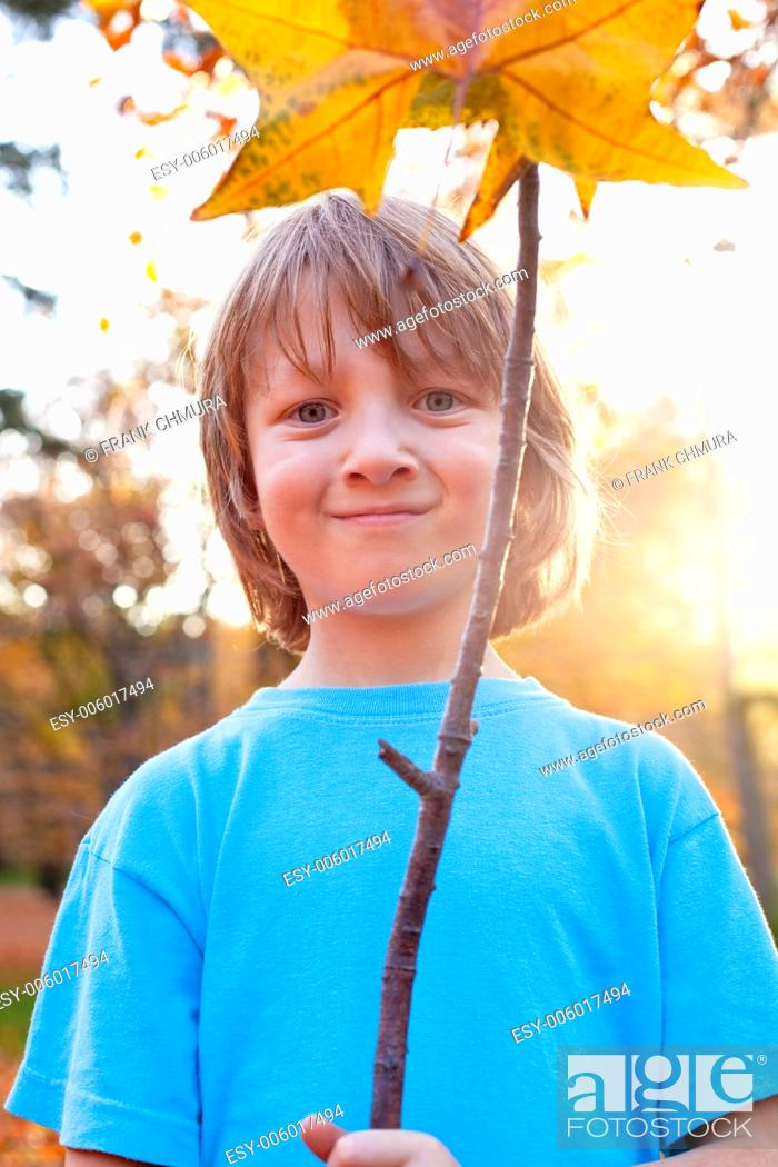 Stock Photo: Portrait of a Boy Holding a Brown Leaf Outdoors.