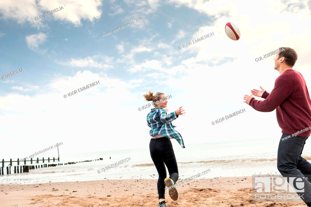 Imagen: Father and daughter playing rugby on beach.