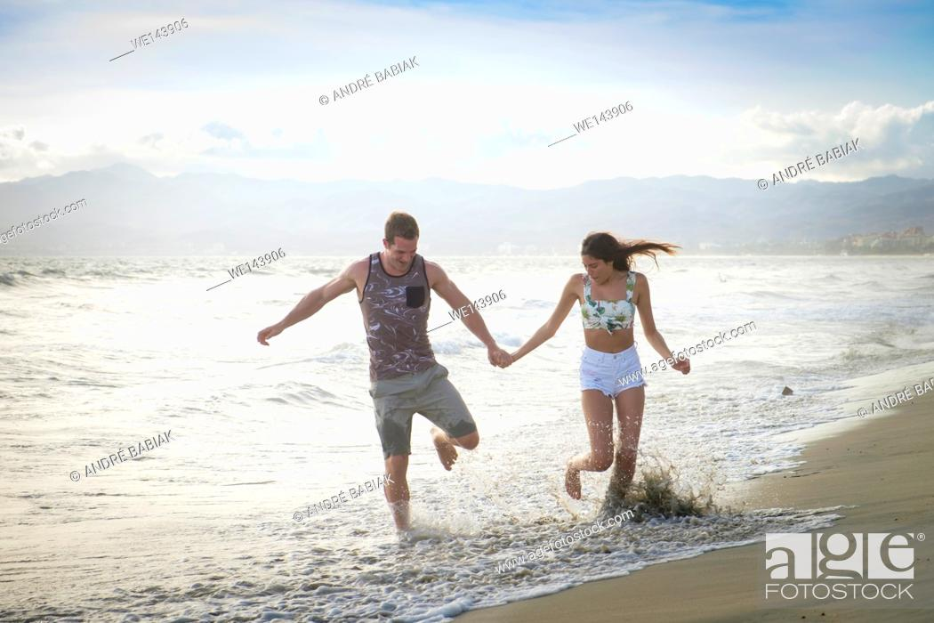 Stock Photo: Young man and woman enjoying a run on the beach, Riviera Nayarit, Mexico.