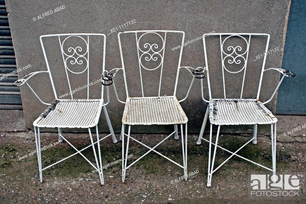 Stock Photo: Three metal white chairs.