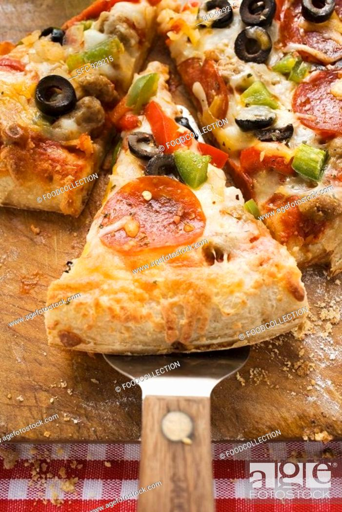 Stock Photo: Piece of pepperoni pizza with peppers and olives on server.