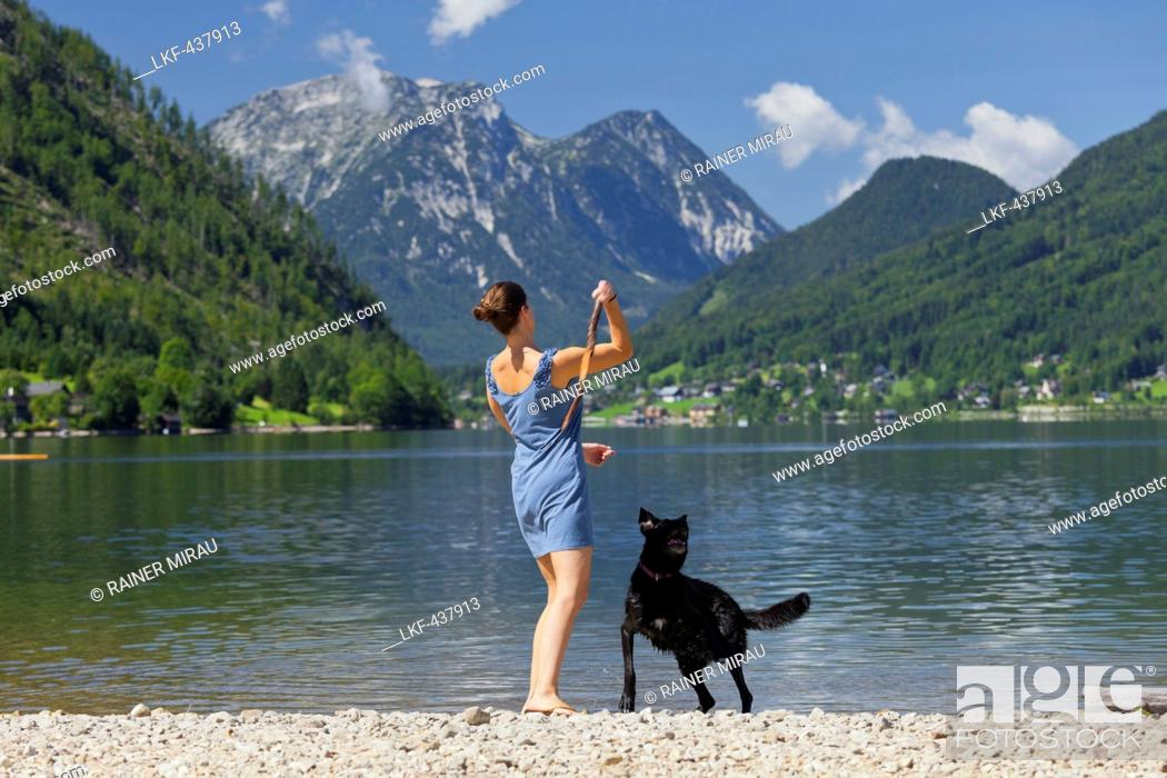Stock Photo: Woman playing with her dog on the shore of lake Grundlsee, Hoher Sarstein, Salzkammergut, Styria, Austria.
