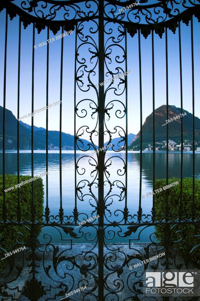 Stock Photo: Switzerland, Ticino, Lake Lugano, Lugano, Parco Civico gate view of Monte San Salvador, dawn.