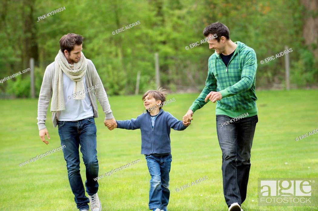 Stock Photo: Boy walking with two men in a park.