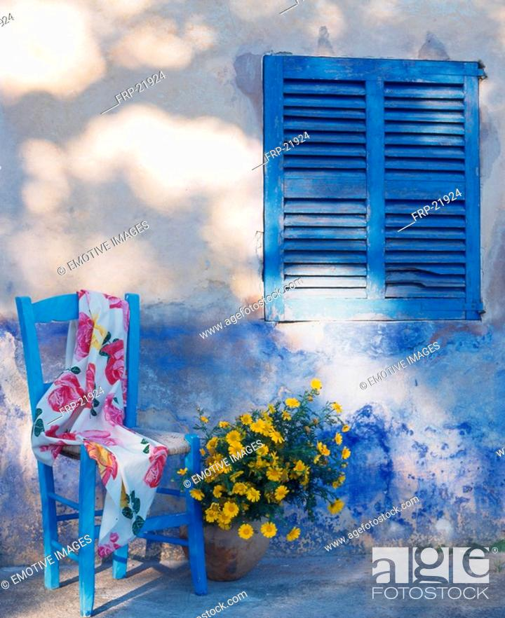 Stock Photo: Blue chair in front of weathered blue wall with shutter.