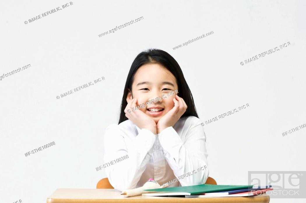 Stock Photo: girl cup her chin in hands.