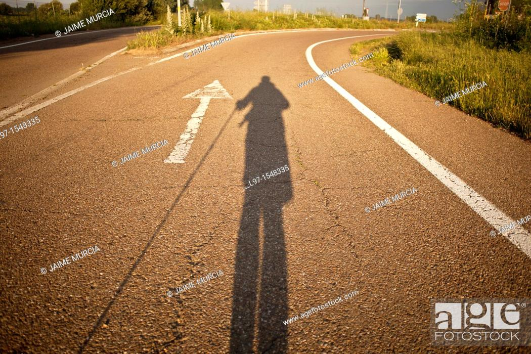 Stock Photo: Early morning shadow of a hiker and white arrow on road along the Camino de Santiago.